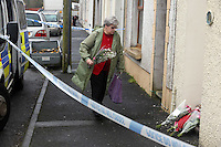 Pictured: An elderly neighbour leaves flowers on the threshold of the family home in Pontyberem, Carmarthenshire, west Wales. Wednesday 19 February 2014 <br />