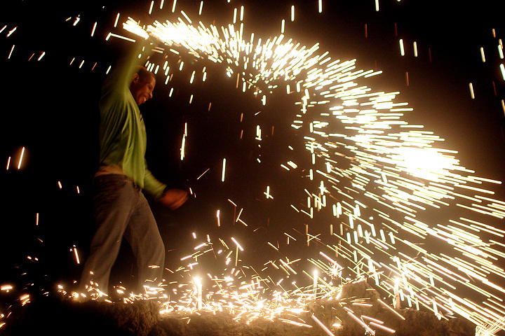 NUQUÍ, EL CHOCO, COLOMBIA -- DECEMBER 8:  A young man celebrates Christmastime and the New Year with fireworks in Nuqui on December 8, 2005. Nuquí is a small town on Colombia's isolated and untamed Pacific coast, an area sandwiched between endless miles of trackless rainforest and the Pacific Ocean. (Photo by Dennis Drenner/Aurora).