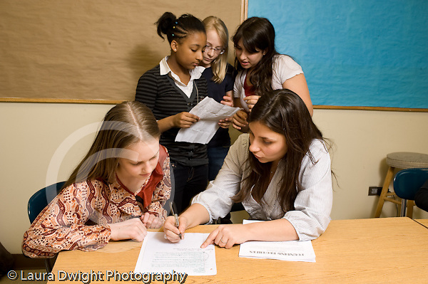 Public Middle School Grade 7 Humanities class female teacher working individually with student as other students work together horizontal