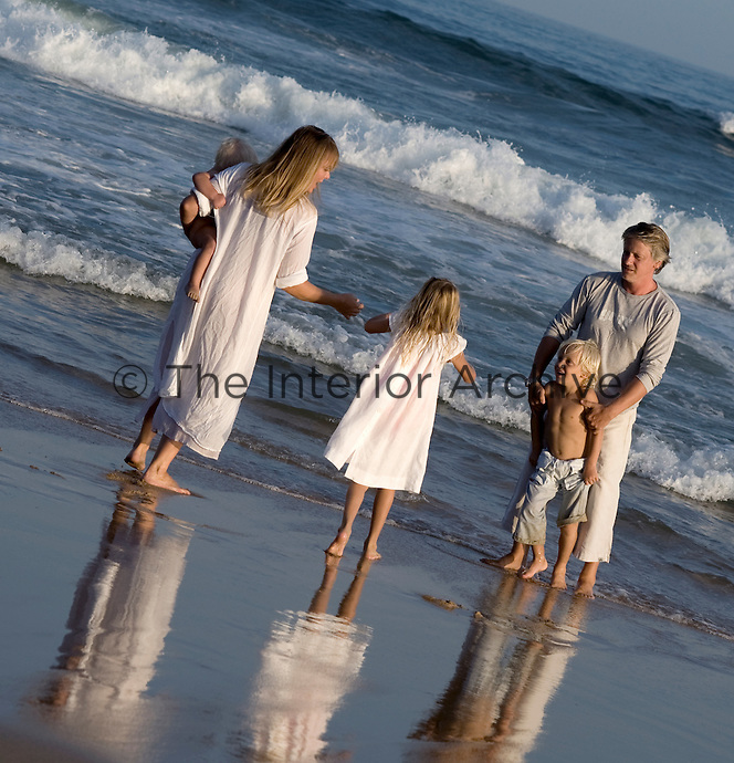 Trevyn McGowan and her husband play with their children on the beach outside their home