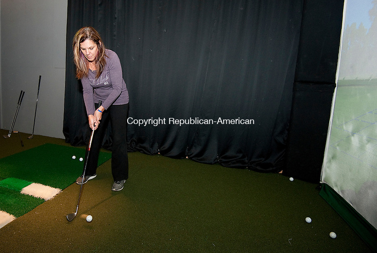 TORRINGTON,  CT-111716JS02-Donna Dutlinger, General Manager of Mulligans, a sports bar and indoor driving range at Eastwoods Country Club in Torrington, demonstrates one of the games  on Thursday. Jim Shannon Republican American