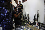 A member of Palestinian security forces inspects weapons and several hand grenades for Palestinian gunmen during operation search in the old city in the west bank city of Nablus August 21, 2016. Palestinian security forces detained two Nablus residents accused of being involved in a shooting on Thursday which left two security officers killed and two others injured, the governor of the northern occupied West Bank city of Nablus. Photo by Nedal Eshtayah