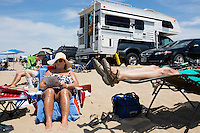 Donna Wells (in hat) and Dana Wells (reclined at right), of Manchester, NH, sit on the beach at Herring Cove Beach in the Cape Cod National Seashore outside of Provincetown, Mass., USA, on Fri., July 1, 2016. Portions of the parking lot have been closed after land eroded during storms earlier this year. The couple estimate they have been coming to this beach for 20 years. In the past, they've taken an RV to the parking lot to sit near it, but this year, due to damage to the parking lot preventing RVs from parking, they had to park in a separate area and walk to the beach.