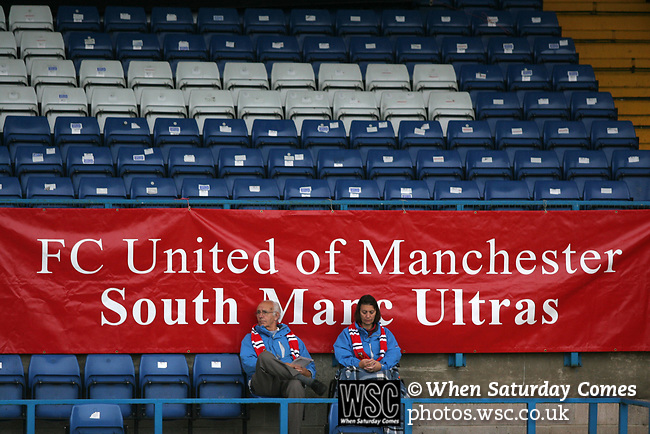 Two fans sitting watching FC United of Manchester take on Glossop North End (blue shirts) in a North West Counties division one match at United's home stadium, Gigg Lane, home to Bury FC. The match was staged on People United Day, an event started in 1999 which brought together fans from across Europe to campaign against racism. FC United were formed in the summer of 2005 by supporters of Manchester United in response to the take over of their club by American millionaire Malcolm Glazer and his family. The club entered the football pyramid at the lowest level with the intention to climbing through the leagues. Photo by Colin McPherson.