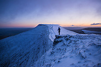 Female hiker looks towards Pen Y Fan at dawn from Corn Du, Brecon Beacons national park, Wales