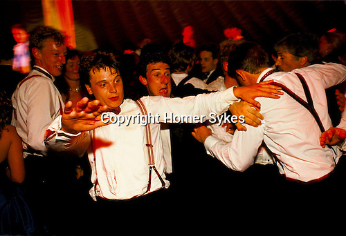 MALE REVELERS DRUNKENLY DANCING TOGETHER AT ROYAL AGRICULTURAL COLLEGE BALL, CIRENCESTER, 1990,