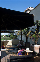 The sunny roof terrace is sheltered by two large parasols and lined with palm trees