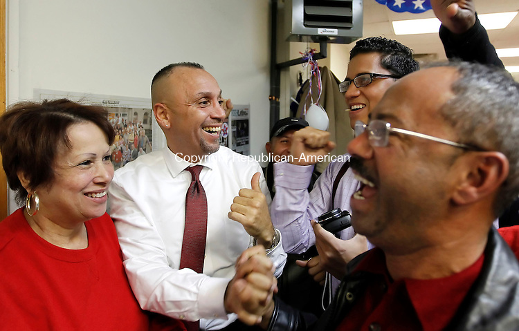 """Waterbury, CT-06 November 2012-110612CM14-  Victor Cuevas, left, Democratic candidate for the 75th District  celebrates with BJ Rodriguez, Team Leader for the 75th District Democratic Town Committee, back right, and Dolly Rosario, of Waterbury below, after at his headquarters Tuesday night in Waterbury.  Cuevas  defeated Republican John """"Jack"""" Alseph Jr.     Christopher Massa Republican-American"""
