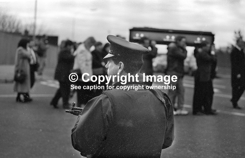 A lone policeman looks on as the funeral cortege of 39 year old Roman Catholic Liam Conway leaves from his family home in Roseleigh Street, Belfast, 24th January 1998. He was murdered by a UFF gunman whilst he was operating a mechanical digger on a pipe laying contract in Ardoyne. 199801240354<br />