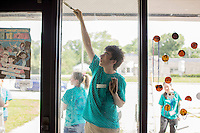 "Members paint the outside of an entryway during ""Circle the City with Service,"" the Kiwanis Circle K International's 2015 Large Scale Service Project, on Wednesday, June 24, 2015, at the Friendship Westside Center for Excellence in Indianapolis. (Photo by James Brosher)"