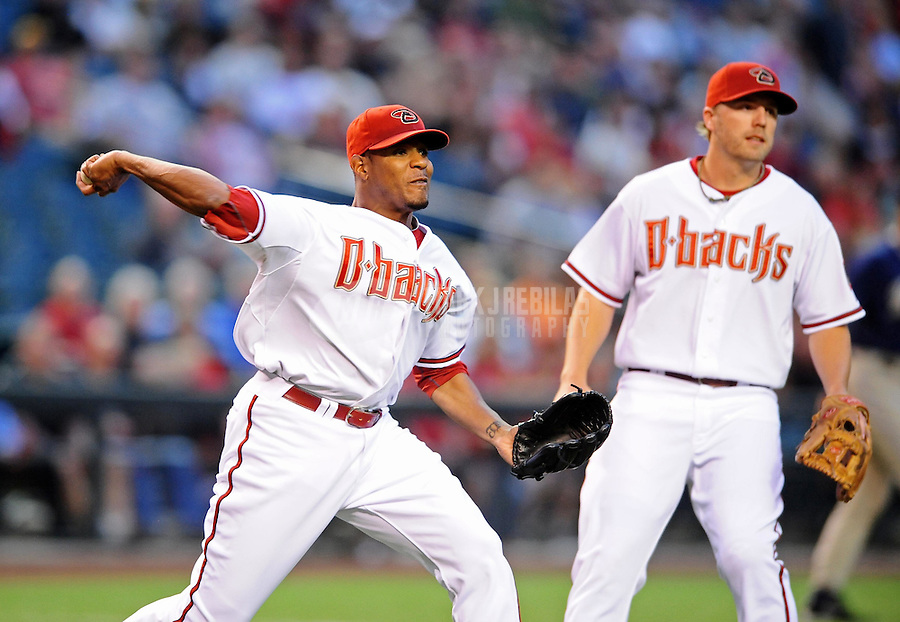 Apr. 6, 2010; Phoenix, AZ, USA; Arizona Diamondbacks pitcher Edwin Jackson throws to first base for an out as third baseman Mark Reynolds looks on against the San Diego Padres at Chase Field. Mandatory Credit: Mark J. Rebilas-