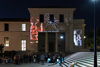 "Opening Reception: ""U-R-U: Aren't You"" presented by Oxy Arts and the Center for Digital Liberal Arts, Nov. 30, 2018 in the Fowler and Johnson Hall courtyard/plaza.<br /> <br /> U-R-U: Aren't You, by Keith Skretch is an outdoor video installation conceived in collaboration with the Oxy Department of Theater's concurrent production of ""U-R-U"", a world envisioned by playwright Julia Lederer where impeccably lifelike robots have relieved humanity of the need to work.<br /> <br /> The 2-channel site-specific architectural video installation, viewable nightly in the Fowler-Johnson courtyard, recasts the building facades as video billboards from an eerily adjacent present, as oversized human forms broadcast the benefits of an artificial life: service, obedience, simplicity. But as humankind's progress lurches drunkenly forward with each new technological novelty, manufactured obsolescence trails close behind.<br /> <br /> The Ettinger Projected Poetry and Art Project is a public art project that infuses the written word and images into everyday moments around campus. Presented nightly for several hours during reading days and finals week each semester through spring 2020, the rotating exhibitions will project provocative and intellectual work on frequently viewed spaces on campus, inspiring deep collaborations between the arts and digital sciences and building pathways and partnerships that mirror our increasingly pluralistic world. The Ettinger Projected Poetry and Art Project is made possible by the generous support of Jane and Bob Ettinger.<br /> (Photo by Marc Campos, Occidental College Photographer)"