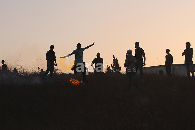 Palestinian protesters stand amid blazes of fire during clashes with Israeli settlers in the West Bank village of Burin on October 3, 2015. Sporadic clashes erupted between Palestinians and a dozen settlers from the settlement of Yitzhar, which is known as a bastion of extremists, when the settlers threw stones at Palestinians who responded in the same way. Photo by Nedal Eshtayah
