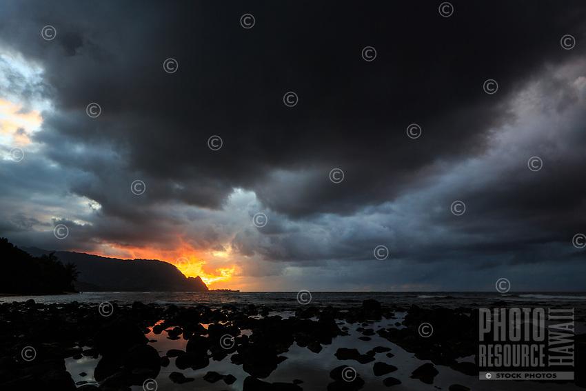 Sunset's colors peek through an ominious sky over Makana, Hanalei Bay and Hideaways Beach, Kaua'i.