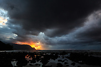 Sunset's colors peek through an ominious sky over Makana, Hanalei Bay and Hideaways Beach, Kaua'i.