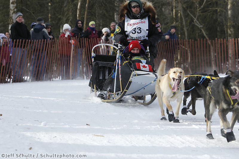 Gerry Willomitzer rounds a corner on the bike trail in mid-town Anchorage during the ceremonial start of the 2011 Iditarod