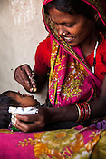 28 year old Asha Devi feeds RUTF to her 11 month daughter, Sharda in her house in Saptari, Nepal. <br /> Asha Devi got married when she was 14. She got pregnant after 6 months of her marriage. Her first child survived for 6 days, she woke up next to a dead baby. She was pregnant two months later. Asha Devi's 2nd daughter survived for 9 months and later died due to prolonged fever. 3 months after her daughter died, Asha was pregnant again and within w months, she had spontaneous abortion. She was pregnant with Radha Kumari mandal who was acutely malnourished. Radha was admitted when she was 36 months old on October, 20th 2013. MUAC - 110 mm, Weight - 7 kg, Height - 75 cm. Radha was discharged on Dec 6, 2013 - her MUAC at the time of discharge was 128mm, Weight 8.8kg and height- 75.5 cm. She consumed 100 sachets of RUTF and gained 5gm/day while on the programme. <br /> Rukmini, her second daughter was born a year after Radha was born. Rukmini was severely malnourished too. She was admitted on Feb 16th, 2014. Her MUAC was 119mm, weight - 11 kg, and height - 96 cm. Her third daughter Sharda is severely malnourished. Sharda is under RUTF.  <br /> Asha Devi is pregnant for the 7th time and is 6 months pregnant.