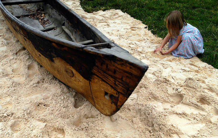 Elise Abbe, from Hamilton, Va., plays in the sand near a canoe on the Mall, part of the annual Smithsonian Folklife Festival being set up. The festival, which opens Thurdays, will focus on Oman, Latino music, American food, and the Forestry Service.