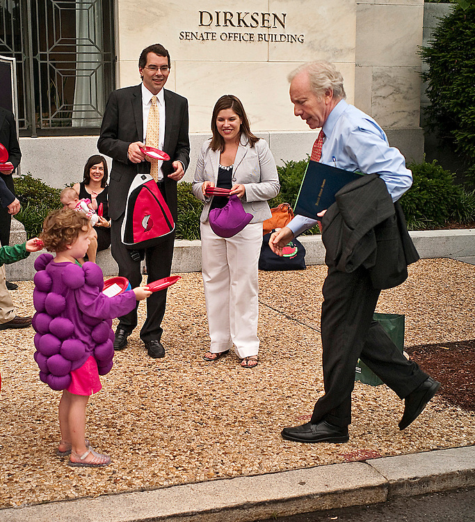 "WASHINGTON, DC - June 16: Bunch-of-grapes Maden Murray, 4, hands a plates with a message attached urging timely passage of a school nutrition bill, to Sen. Joseph I. Lieberman, I-Conn., as arrives for work at the Dirksen Senate Office Building. The Center for Science in the Public Interest organized the push to get the ""Healthy, Hunger-Free Kids Act"" (S. 3307) to the Senate floor this month. The message glued to each plate, which were red and blue respectively, was headlined, ""Congress has a lot on its plate, but it needs to address what's on kids' plates - now!"" (Photo by Scott J. Ferrell/Congressional Quarterly)"