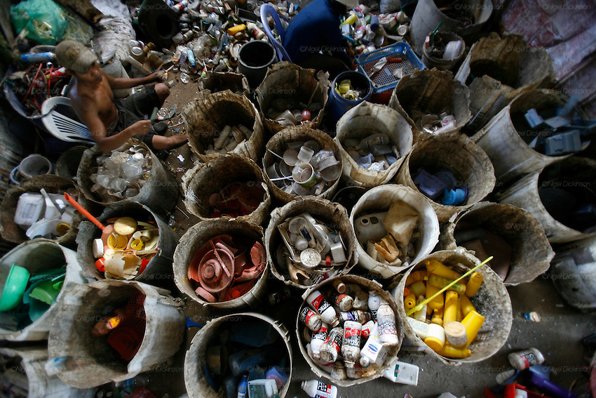 Like an artist's palette, recycling workers sort the different colours, textures, and weights of plastic into different buckets. Recycling warehouse for plastics. The plastics are sorted by recycling workers earning less than a dollar day. They throw platsic of different textures and colours into various buckets. These are collected and placed into larger sacks. The plastic is then put through a mincer (like making minced meat for hamburgers) and the small crushed picese of plastic mixed with water in the process are then dried on mats in the sun, like for coffee beans. The dry plastic shavings are bagged and shipped off for export to Thailand and Vietnam