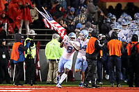 RALEIGH, NC - NOVEMBER 30: Michael Carter #8 of the University of North Carolina leads his team onto the field carrying the American flag during a game between North Carolina and North Carolina State at Carter-Finley Stadium on November 30, 2019 in Raleigh, North Carolina.