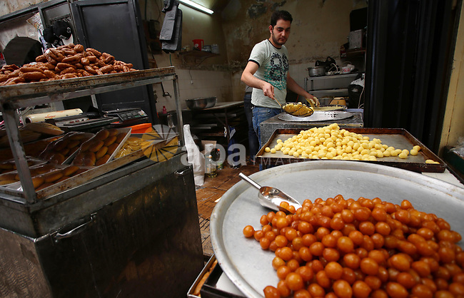 A Palestinian vendor prepares sweets on the Muslim holy fasting month of Ramadan at his shop in the Old City of the West Bank town of Nablus on May 28, 2017. Ramadan is sacred to Muslims because it is during that month that tradition says the Koran was revealed to the Prophet Mohammed. The fast is one of the five main religious obligations under Islam. More than 1.5 billion Muslims around the world will mark the month, during which believers abstain from eating, drinking, smoking and having sex from dawn until sunset. Photo by Ayman Ameen