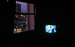 Downtown Hotel room at night with tv on with city lights