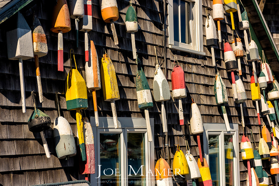Lobster bouys adorn the side of a traditional cedar shaked building along the coast of Maine.