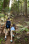 An eight year old boy helps a six year old girl (brother and sister) up a steep trail in Bonner County, Idaho.