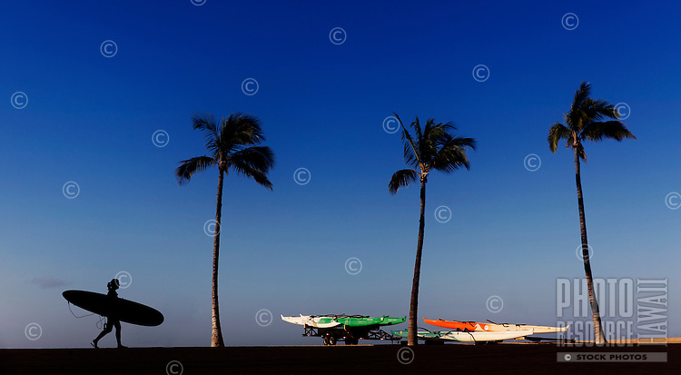 A woman with her surfboard walking in silhouette against a blue sky at sunrise, O'ahu.