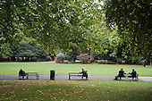 People sitting on park benches in Lincoln's Inn Fields, London