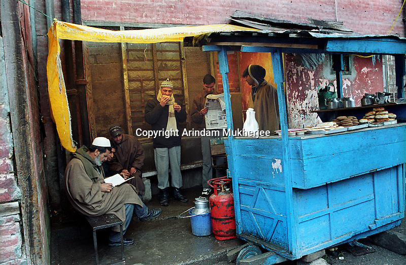 People have their breakfast at a tea stall in a lane of Srinagar, Kashmir valley, India