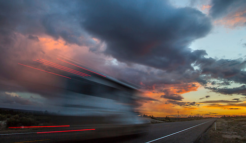 A motor home drives towards the setting sun in Southern Utah