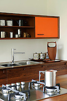 A teak ice bucket with an orange liner designed by Jens Quistgaard is the inspiration for a kitchen in a Scandinavian Modern style. The wooden kitchen units were handmade in water-resistant iroko with orange laminate on the door fronts and chamfered edges.