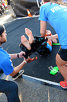 Volunteers help swimmers out of their wetsuits during the 2015 Ironman competition on Sunday, September 13, 2015 in Madison, Wisconsin