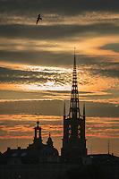 Riddarholmskyrkan i Stockholm mot gul molnhimmel vid solnedgång
