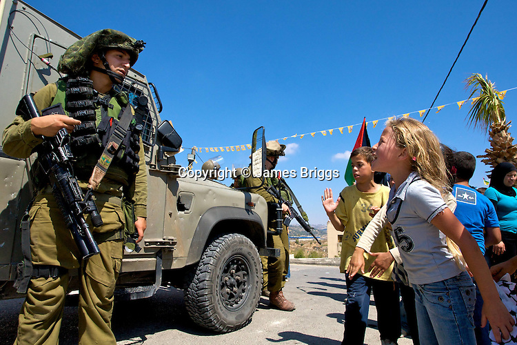 Young Palestinian children jeer at Israeli soldiers following the pursuit of stone throwing Palestinian youths into the West Bank village of Nabi Saleh near Ramallah on 02/07/2010.