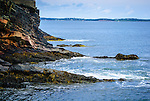 Rugged shoreline at The Ovens, Nova Scotia, with sailboats and opposite shore in the distance