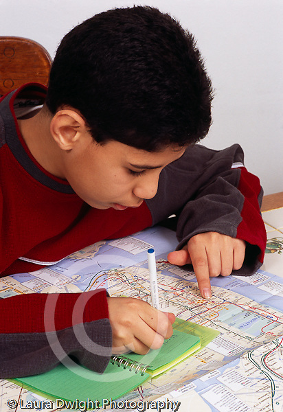 12 year old boy looking at subway map, planning trip, writing down directions