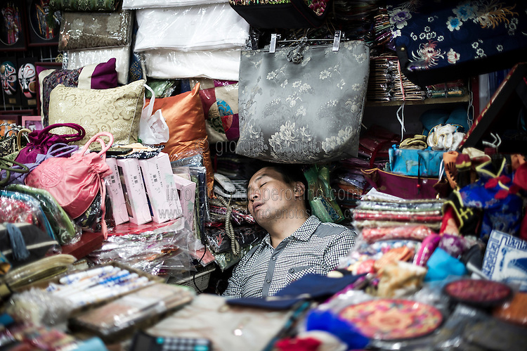 """A Chinese vendor takes a rest in his souvenir gift shop at the Silk Market in Beijing, China, July 20, 2014.<br /> <br /> This image is part of the series """"24/7"""", an ironic view on restless and fast-growing Chinese economy described through street vendors and workers sleeping during their commercial daily activity. <br /> <br /> © Giorgio Perottino"""