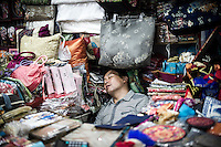 "A Chinese vendor takes a rest in his souvenir gift shop at the Silk Market in Beijing, China, July 20, 2014.<br /> <br /> This image is part of the series ""24/7"", an ironic view on restless and fast-growing Chinese economy described through street vendors and workers sleeping during their commercial daily activity. <br /> <br /> © Giorgio Perottino"