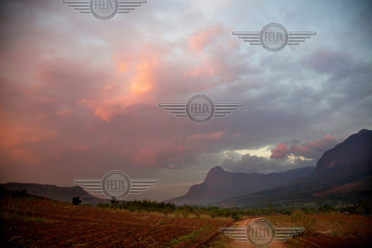 An unpaved road runs through cultivated fields with Mulanje Mountain rising on the horizon.