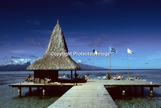 A pier with sunbathers on April 23, 1997 at an exclusive resort on Bora Bora, a paradise island in French Polynesia. The Island is a playground for rich tourists and Hollywood stars as it provides total security and privacy. Most local people live of the tourism industry and usually work in one of the luxury resorts. (Photo by: Per-Anders Pettersson)