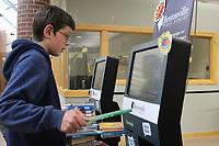 NWA Democrat-Gazette/MARY JORDAN @NWAMARYJ Homeschooler Dalton Mason, 12, of Hiwasse uses a scanning station to check out books Thursday at the Bentonville Public Library.