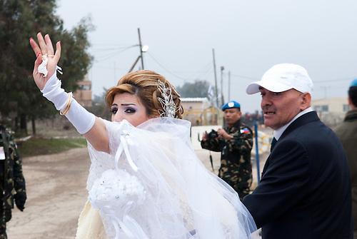 Plateau du Golan, dans la zone tampon entre la Syrie et Israel, Jan 2011. Dans le cadre de la reunification familiale facilitee par le CICR (Comite International de la Croix Rouge), un mariage a lieu entre une Syrienne et un  Israelien de la comunaute druze, qui est separee des deux cotes de la frontiere.  Le temps d'une petite heure, c'est une occasion unique de revoir des parents qui vivent de l'autre cote de la frontiere depuis qu'Israel a annexe le Golan en 1981 (annexion non reconnue a ce jour par l'ONU). Seul le CICR est habilite a coordoner ce genre de reunion, car la frontiere est fermee pour les civils. Samar et Nabih passent ensemble la fontiere apres avoir dit adieu a la famille de Samar qui retourne du cote Syrien.