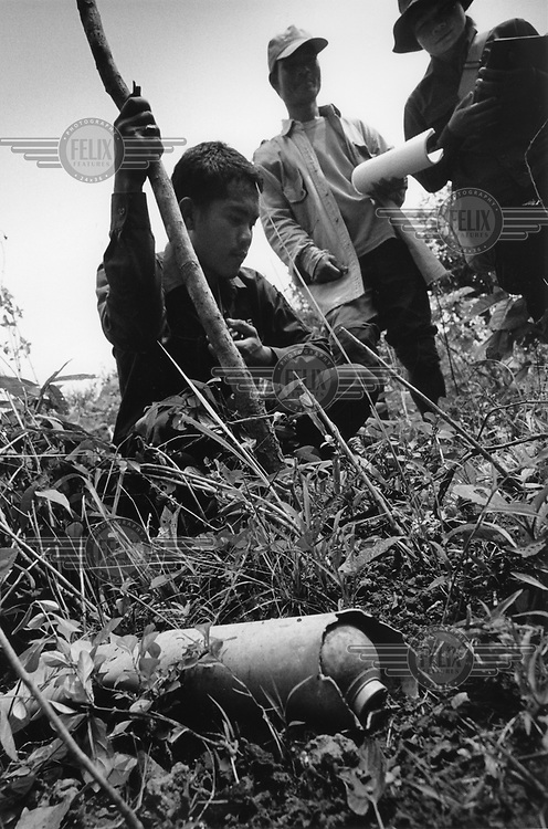 A Mines Advisory Group (MAG) Community Liaison team prepare to mark a tube dispenser full of BLU 24B submunitions. There were another five tubes nearby suggesting that a complete rack of clusterbombs were dropped at the spot. More than two million tonnes of ordnance was dropped over Laos ruring the Second Indo-China War, an estimated 30 per cent of which did not explode on impact. UXO still affects more than 25 per cent of Lao villages