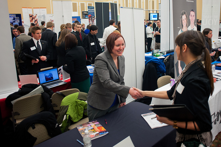 Megan Paskins (center) greets Morgan Meade (right) at her booth during the Spring Career and Internship Fair. Photo by: Ross Brinkerhoff.