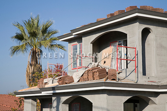 Fresh light grey stucco covers wire mesh on the walls and red brick roof tiles lie in stacks on the roof of a new single family home under construction in California.