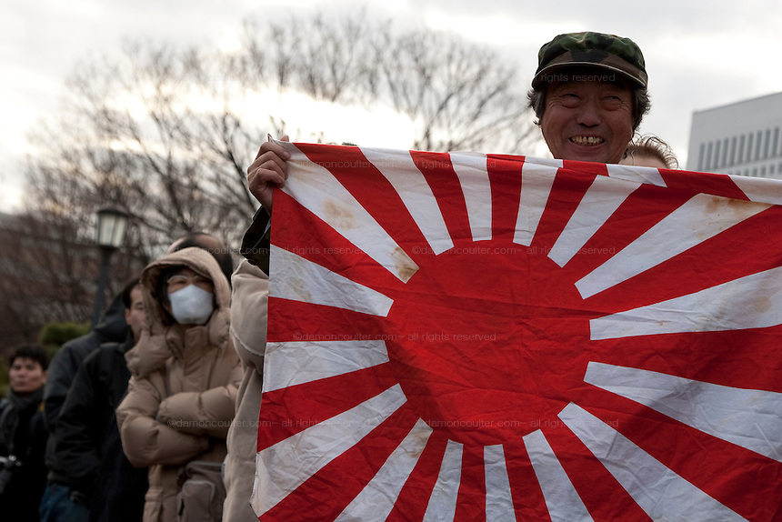 A Japanese man wearing a camoflaged army hat army hat displays a Japanese battle flag in a park near the Imperial palace on the occasion of Emperor Akihito's traditional birthday address at the Royal Palace, Tokyo, Japan. December 23rd 2008
