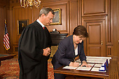 Chief Justice John G. Roberts, Jr., looks on as Associate Justice Elena Kagan signs the Oaths of Office in the Justices' Conference Room at the Supreme Court Building..Mandatory Credit: Steve Petteway - US Supreme Court via CNP
